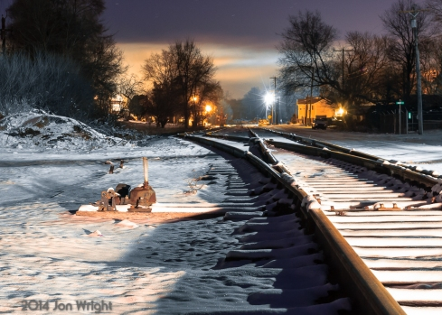 """A recent snow event the previous day makes for some """"cool"""" scenes like this one looking North at the old Norfolk & western/Baltimore and Ohio Railroad Interchange Yard. The temperature at the time this was taken was holding at a steady 9 degrees on the evening of Friday January 3rd, 2014. The scene is lit by the headlights of my parked car behind me to the right, an overhead street light and in the distance, smoke from a house's fireplace lit up by perimeter lights from the neighbors house. The interchange was used until the early 2000's when NS switched the interchange to Hagerstown via Vardo yard and the acquisition of Conrail. It is now used for storing MoW equipment. New siding and interlocking work at Daniels and Shen are underway. The look you see here may change dramatically."""