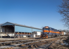 THE ENGINE SHED: PASSING THROUGH THE YARD, UBEG PASSES THE ENGINE SHED HOUSING MMID 303 STILL SHOWING HER BLUE AND ORANGE... FOR NOW. 1/16/14