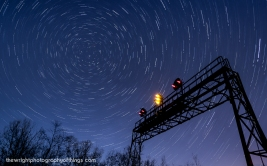 """SIGNAL TO THE STARS Twenty-Seven and a half minutes elapse in this collection of four shots layered together as the Pennsy signal bridge at AR (Allegheny Range) stands tall against the backdrop of the swirling night sky and the North Star. This signal stands close to the Pennsylvania Railroad's summit across the Eastern Continental Divide 2,167 feet above sea level and lets eastbound crews know half the journey over the mountains is complete before they enter Portage Tunnel and into """"The Slide"""" and down the mountain."""