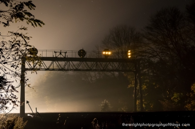 The PRR Position Light Signals at Lilly, PA overnight in October, 2017 as the light from an approaching eastbound pierces through the night air and stars slowly fade. Of note is the contraption to the left center of an old pulley system used by the PRR to allow water to the locomotives since Lilly was a water stop and full interlocking on the West Slope.