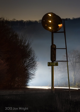 FOGGY CLEARANCE: A quiet night along Norfolk Southern's Middle Division of the Pittsburgh Line is on break as an eastbound approaches the block from the west and lights up the PRR position Light signals and a westbound intermodal train prepares to round the curve illuminating the fog and tracks ahead silhouetting the mast signal.