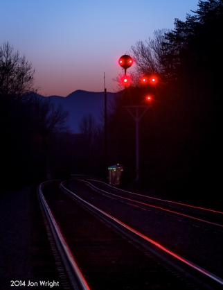 ACORN HILL AT DUSK: The peaks of Massanutten Mountain loom behind the N&W color position light signals that guard the interlocking at the south end of the Bentonville siding in the Shenandoah Valley of Virginia.
