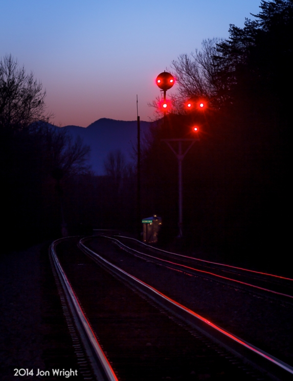 H73.4 ACORN HILL AT DUSK: The peaks of Massanutten Mountain loom behind the N&W color position light signals that guard the interlocking at the south end of the Bentonville siding in the Shenandoah Valley of Virginia.