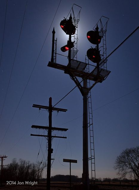 The N&W Shenandoah Junction CPL Signal Bracket Mast and code line pole is silhouetted against overnight sky lit up by the Full Moon of March 2014.