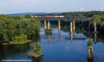 Of the many bridges that span the Potomac River here, only 2 are active. In the foreground are the remains of a prior road bridge that connected Maryland on the left and West Virginia on the right. The higher further piers are what remains of the old Shenandoah Valley Railroad bridge that stood until 1917. Finally, the present and former Norfolk and Western railroad bridge that Norfolk Southern train 13R is seen high above the water. Another bridge stood in the immediate foreground but was totally demolished upon completion of the currentroad