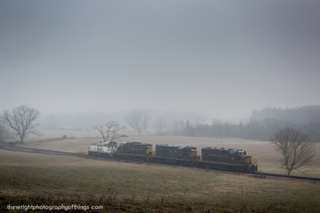 """SANDMAN'S FOGGY DAYS Winchester and Western's """"Sandman"""" out of Gore, VA has seen better days. With fuel prices at a steady low, Unimin, it's parent company and biggest customer has been trucking many loads out of the mine leaving the railroad with odd and end jobs. Today it leaves with WW 1200 in tow after being serviced and being returned to the Essroc plant in Martinsburg, WV where it now see's its regular service. The train is rolling down Gainesboro Hill just south of it's namesake town."""