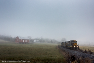 """FOGGY GLIMPSE A scene eerily gloomy as the fog stuck close to teh ground. The Winchester and Western """"Sandman"""" rounds the sweeping curve as it navigates the original WW line built a century ago downgrade from Gainesboro and approaches the Hogue Creek Valley."""
