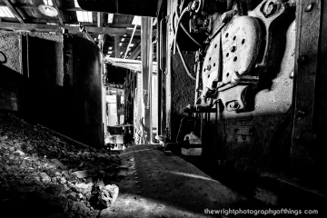 "COLD FIRE - Coal sits on the floor of the cab of EBT 12 aka ""Millie"" awaiting its turn to burn inside the firebox during a recent Spring afternoon inside the railroad's roundhouse."