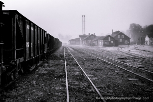The Sun has burnt off enough fog to shine on the sides of the shop buildings at the East Broad Top Railroad. A string of coal hoppers sit in the yard having not seen any revenue service in 60 years.