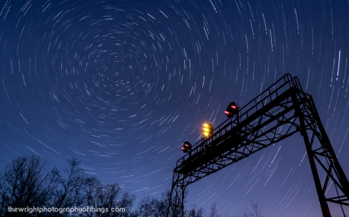 """Twenty-Seven and a half minutes elapse in this collection of four shots layered together as the Pennsy signal bridge at AR (Allegheny Range) stands tall against the backdrop of the swirling night sky and the North Star. This signal stands close to the Pennsylvania Railroad's summit across the Eastern Continental Divide 2,167 feet above sea level and lets eastbound crews know half the journey over the mountains is complete before they enter Portage Tunnel and into """"The Slide"""" and down the mountain."""