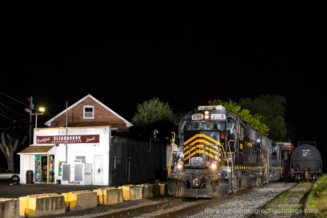 The Winchester and Western switcher passes by the Clearbrook Shopping Center Convenience Store as it approaches US Route 11. Off to the right on the Lane siding are oil tankers for Flying J located a few miles to the North.